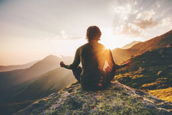Man meditating on mountain
