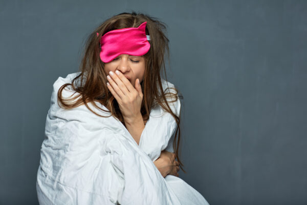 Woman with weighted blanket and eye mask